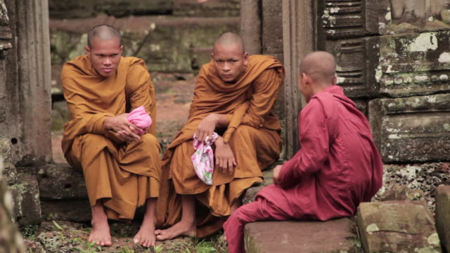 Three Buddhist monks sit at the Angkor Wat Temple, Cambodia.