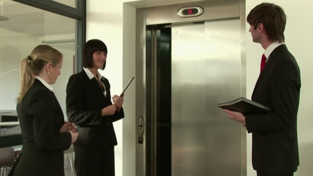 ms three business collegues waiting for and then boarding elevator / kinsale, ireland - coda di cavallo video stock e b–roll
