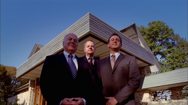 ms, la, pan, three business men standing outside house, portrait, usa, pennsylvania, solebury - 薄毛点の映像素材/bロール