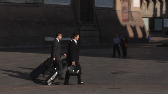 ws pan three business men walking through plaza with luggage / bologna, italy - kompletter anzug stock-videos und b-roll-filmmaterial