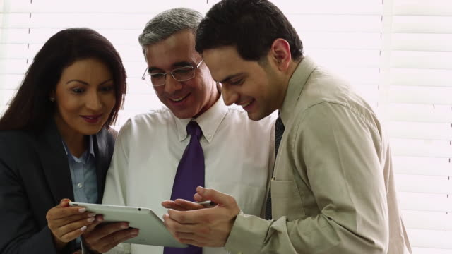 Three business people holding a digital tablet and discussing