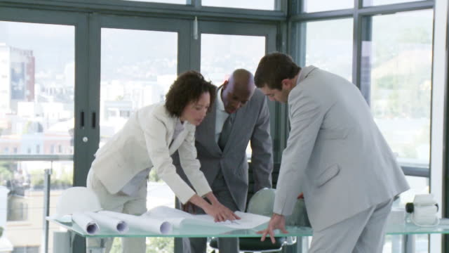 ms three business people looking at plans in office, cape town, south africa - einzelne frau mit männergruppe stock-videos und b-roll-filmmaterial