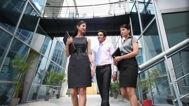 vídeos de stock e filmes b-roll de three business people talking  - camisa e gravata