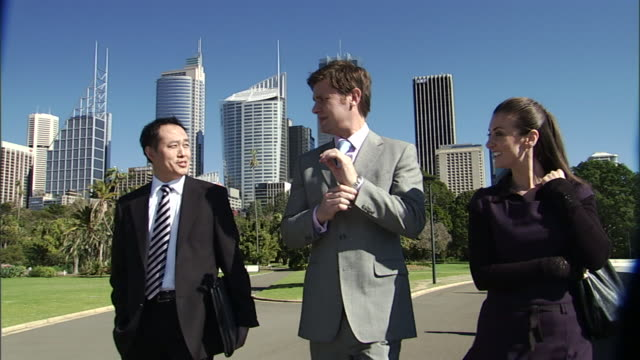 CU, Three business people walking and talking outdoors, office buildings in background, Sydney, Australia