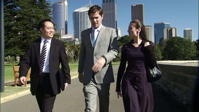 cu, three business people walking and talking outdoors, office buildings in background, sydney, australia - einzelne frau mit männergruppe stock-videos und b-roll-filmmaterial