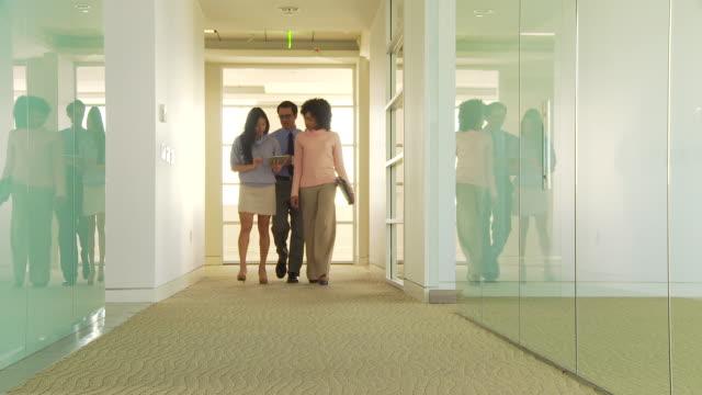 Three business people walking down hallway