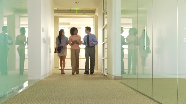 Three business people walking down hallway