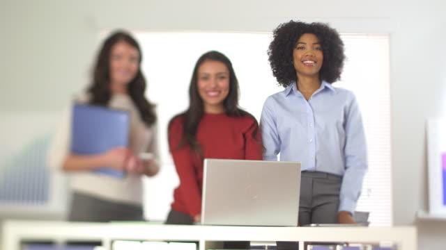 three business woman smiling at camera - weibliche angestellte stock-videos und b-roll-filmmaterial