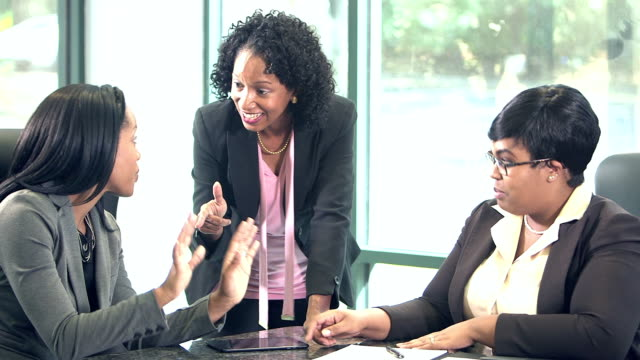 Three business women conversing in board room