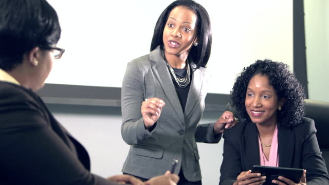Three business women conversing in board room