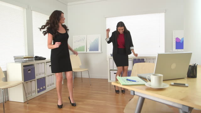 Three business women dancing in office