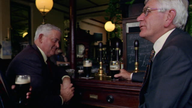 three businessmen drinking dark beer, talking + laughing at bar / dublin, ireland - pub stock videos & royalty-free footage