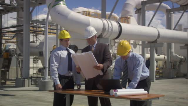 ms three businessmen looking at blueprint and using laptop outside oil refinery / vista del mar, california, usa - mar bildbanksvideor och videomaterial från bakom kulisserna