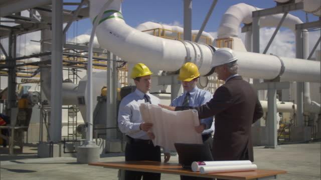 MS Three businessmen looking at blueprint outside oil refinery / Vista del Mar, California, USA