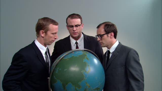 stockvideo's en b-roll-footage met ms three businessmen posed around globe, talking and pointing to different places/ men laughing, joking, and greedily rubbing hands together / new york city - bureauglobe