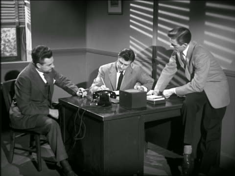 b/w 1949/50 three businessmen sitting at desk having meeting / one man is writing in book - employee engagement stock videos & royalty-free footage