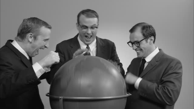 B/W MS three businessmen spinning globe around and making funny faces/ New York City