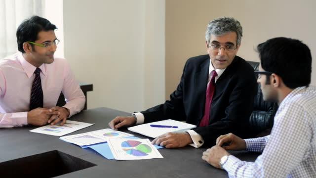 ms three businessmen talking each other in meeting in office / india - abbigliamento da lavoro formale video stock e b–roll