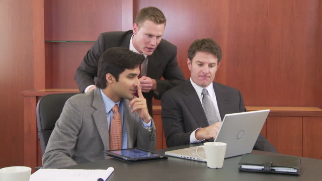 Three businessmen working at table