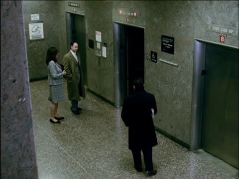 ha ws three businesspeople entering elevator in lobby followed by jogger / brooklyn, new york, usa - coda di cavallo video stock e b–roll