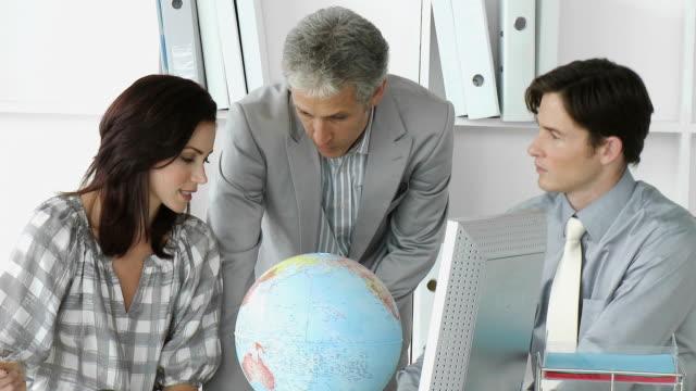 vídeos y material grabado en eventos de stock de ms three businesspeople talking at desk with computer and globe / cape town, western cape, south africa - globo terráqueo para escritorio