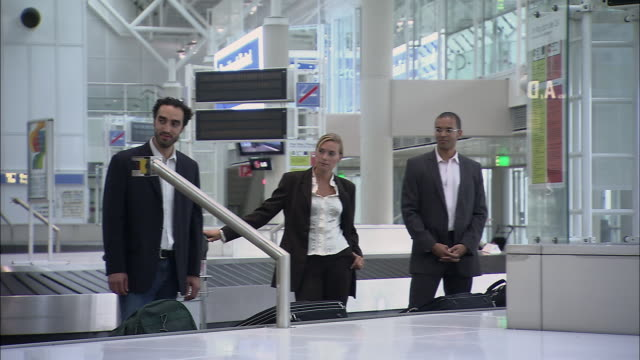 ms pan three businesspeople watching couple wearing sombreros and playing maracas near baggage claim carousel / munich, germany - geschäftsreise stock-videos und b-roll-filmmaterial