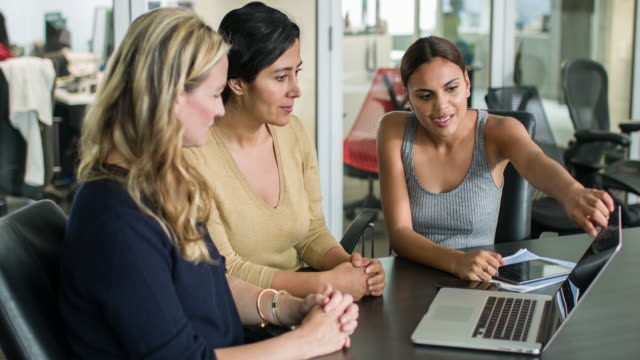 three businesswomen discussing some project on a laptop - indigenous culture stock videos & royalty-free footage