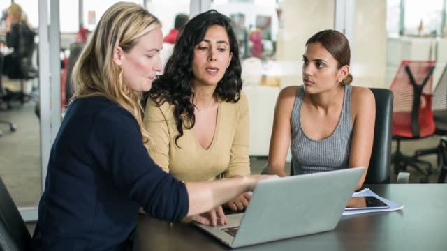 Three businesswomen discussing some work using the laptop