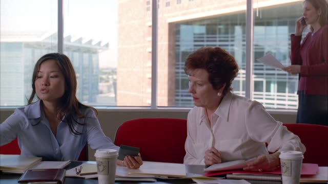 Three businesswomen meet in a conference room.