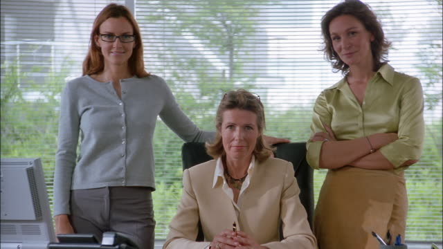stockvideo's en b-roll-footage met three businesswomen pose behind a desk in an office. - directrice