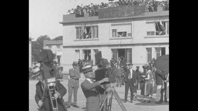 three cameramen outside building at airport getting cameras ready to shoot footage of four us army air service airplanes arriving in paris during... - newsreel stock videos & royalty-free footage