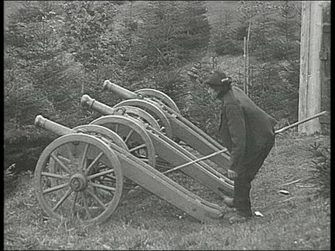 three cannons lined up in a row man stands behind and fires them man firing three cannons on january 01 1910 in oberammergau germany - 1910 stock-videos und b-roll-filmmaterial