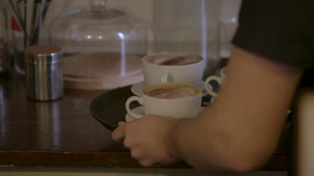 cu three cappuccinos are carried on a tray - three objects stock videos & royalty-free footage