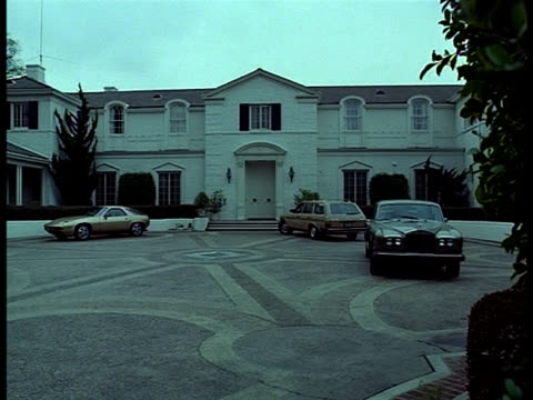 three cars are parked on a sculptured driveway in front of a two-story mansion. - stately home stock videos & royalty-free footage