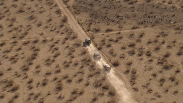 three cars follow a dirt road through the desert. - crossroad stock videos & royalty-free footage