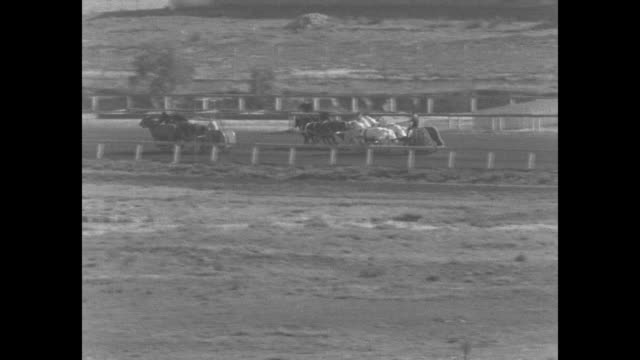three chariot teams, representing egypt, persia, and greece, race on track at agua caliente, mexico / chariots in the backstretch / chariot teams... - agua点の映像素材/bロール