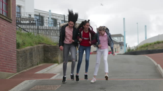 three cheerful teenage girls arm in arm - skipping along stock videos & royalty-free footage
