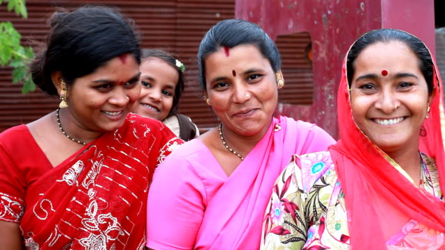 Three cheerful traditional Indian Women with a Girl
