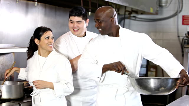 Three chefs cooking and talking in restaurant kitchen