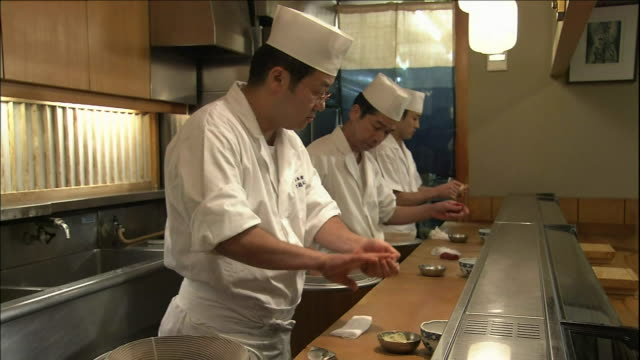three chefs preparel sushi ovals behind the counter of a sushi shop. - sushi video stock e b–roll
