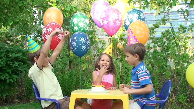 three child at a birthday party in the garden - party hat stock videos and b-roll footage
