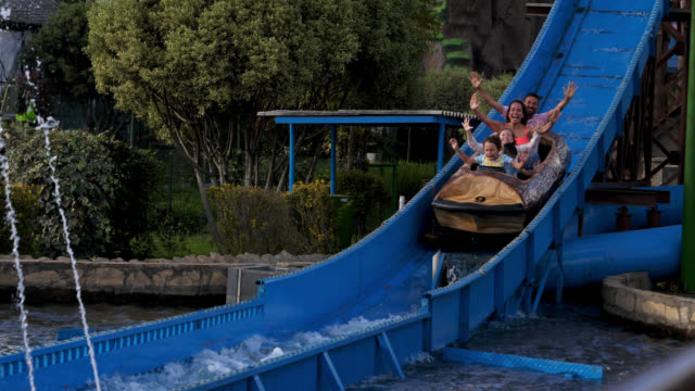 three children and parents on a log ride at an amusement park having fun - water slide stock videos & royalty-free footage