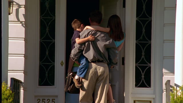 Three children and their mother happily greet Dad when he arrives home.