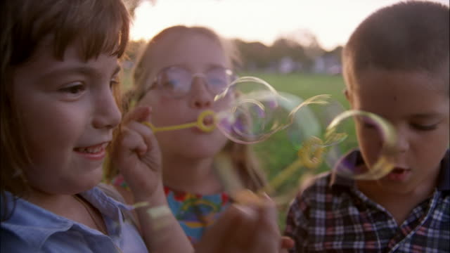 Three children blow bubbles at the camera.
