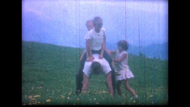 1966 three children climb all over man in swiss alp flower field - 肩に乗せる点の映像素材/bロール