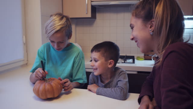 Three children drawing on halloween pumpkin