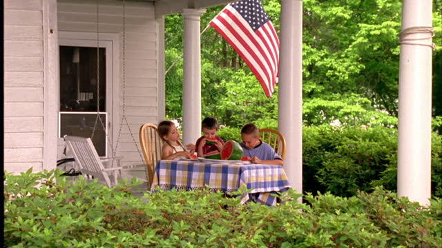 Three children eat watermelon at a table on a porch.