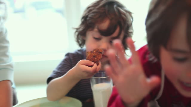 CU FOCUSING Three children (4-5, 6-7, 8-9) eating fresh baked cookies, Yarmouth, Maine, USA