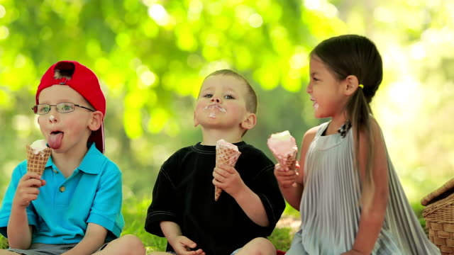 three children have fun eating ice cream - ice cream cone stock videos & royalty-free footage