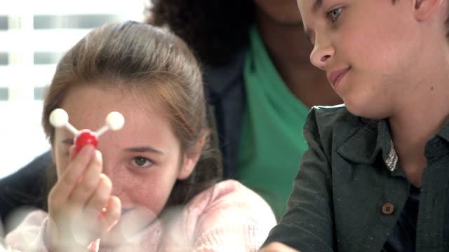 drei kinder im naturwissenschaftlichen unterricht mit molekülmodell - 10 11 jahre stock-videos und b-roll-filmmaterial